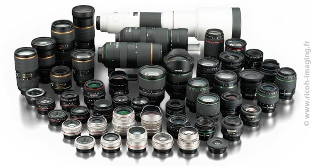 Collection d'optiques Pentax de toutes tailles pour illustrer l'article sur les sigles et abréviations des objectifs Pentax