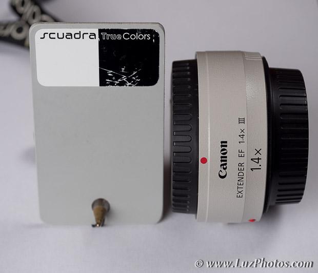 Photo du multiplicateur Canon Extender EF 1.4x III à côté d'une charte gris neutre